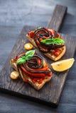 2 bruschettas с испеченными aubergines и перцами на черной предпосылке Стоковая Фотография RF