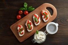 Bruschettas con queso, el tomate y la albahaca en tabla de cortar en fondo rústico de madera Imagenes de archivo