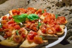 Bruschettas italianos con el tomate tajado y la albahaca listos para el brea imagenes de archivo