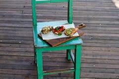 Bruschettas med den röda fisken och en gurka, banan med jordnötdeg och mandlar, tomat med en gurka arkivfoton