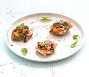 Bruschettas with Prosciutto, roasted melon, soft cheese and basil on white ceramic plate over light blue background Royalty Free Stock Photos