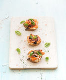 Bruschettas with Prosciutto, roasted melon, soft cheese and basil on wooden serving board over light blue background Stock Photo