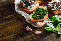 Bruschettas with Some Ingredients. On Wooden Table stock images