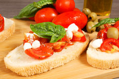 Bruschette. With juicy tomatoes on fresh bread, pesto as topping Stock Photo