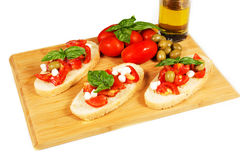 Bruschette. With juicy tomatoes on fresh bread, pesto as topping Royalty Free Stock Images