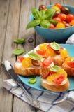 Bruschette avec du feta et des tomates-cerises sur le fond en bois Photos libres de droits