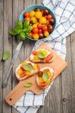 Bruschette avec du feta et des tomates-cerises sur le fond en bois Image stock
