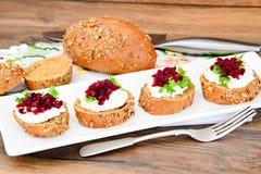 Bruschette avec du fromage de chèvre, l'Arugula et la betterave Photographie stock