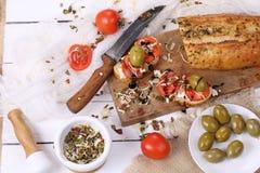 Bruschette avec les tomates et le fromage de chèvre et les olives Photo stock