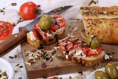 Bruschette avec les tomates et le fromage de chèvre et les olives Images libres de droits