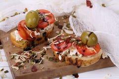 Bruschette avec les tomates et le fromage de chèvre et les olives Image libre de droits