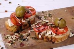 Bruschette avec les tomates et le fromage de chèvre et les olives Photos stock