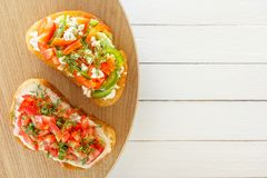 Bruschette avec les tomates fraîches, le poivron doux et le fromage de chèvre sur les conseils blancs Photographie stock libre de droits