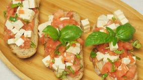 Bruschette avec les tomates, le basilic et le fromage banque de vidéos