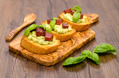 Bruschette with avocado cream and sausage Royalty Free Stock Photo