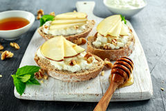 Bruschette d'apéritif avec le fromage de poire, de miel, de noix et blanc sur le conseil blanc Photos stock