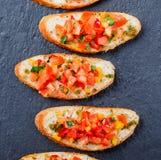 Bruschette d'apéritif avec les légumes coupés sur le pain de ciabatta sur la fin en pierre de fond d'ardoise  Image libre de droits