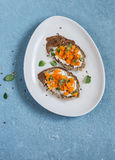 Bruschette de potiron d'un plat blanc sur un fond bleu Petit déjeuner, casse-croûte ou apéritif sain Images libres de droits