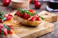 Bruschette de tomate et de basilic avec du pain à l'ail grillé Photos stock