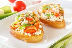 Bruschette deux avec le poivron doux et le fromage de chèvre rouges dans un plat à côté des légumes frais sur les conseils blancs Image libre de droits