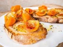 Bruschette grillée de pain avec les tomates italiennes, la couleur orange, très bon et durable, assaisonné avec l'huile d'olive e photographie stock