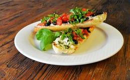 Bruschette italienne de tomate avec des olives sur en bois Photographie stock