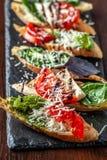 Bruschettes italianos com mozzarella, tomates, molho do pesto e queijo parmesão, em uma pedra preta, em uma tabela de madeira Cop fotos de stock royalty free