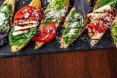 Bruschettes italianos com mozzarella, tomates, molho do pesto e queijo parmesão, em uma pedra preta, em uma tabela de madeira Cop fotografia de stock