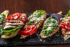 Bruschettes italianos com mozzarella, tomates, molho do pesto e queijo parmesão, em uma pedra preta, em uma tabela de madeira Cop fotos de stock
