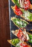 Bruschettes italianos com mozzarella, tomates, molho do pesto e queijo parmesão, em uma pedra preta, em uma tabela de madeira Cop imagem de stock