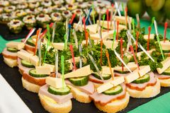 Bruschetti or canapes with cheese, olives, ham, cucumber royalty free stock photography