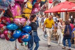 BRUSELAS, BÉLGICA - 6 DE SEPTIEMBRE DE 2014: La mujer joven desconocida que vende el ` s de los niños hincha en una calle en el c imagen de archivo libre de regalías