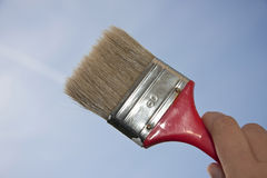 Brush. Hand is holding a brush against the sky Royalty Free Stock Photo