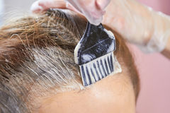 Brush applying hair dye. Hair close up royalty free stock photo