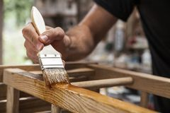 Brush applying varnish. Hand holding a brush applying varnish paint on a wooden furniture Royalty Free Stock Photos