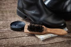 Brush with black boot and polish cream Stock Images