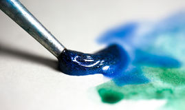 Brush with blue and green watercolor. Painting something abstract on white paper royalty free stock photos