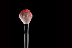 Brush with blush. Make-up brush with red blush on black, close-up Royalty Free Stock Photo