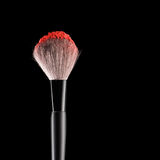 Brush with blush. Make-up brush with red blush on black, close-up Stock Images