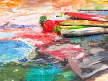 Brush and bright oil-paint palette for background Stock Photography