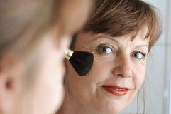 Brush at the cheek. Attractive middle-aged woman applying makeup to her cheek Stock Image