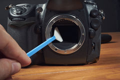 Brush for cleaning digital camera with hand Royalty Free Stock Photography