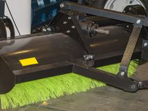 Brush for cleaning the street. A green brush in a black metal frame attached to a tractor for cleaning the street Stock Photography