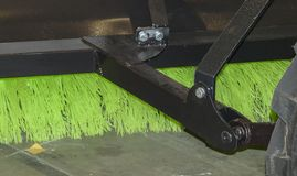 Brush for cleaning the street. A green brush in a black metal frame attached to a tractor for cleaning the street Royalty Free Stock Photos