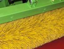 Brush for cleaning the street. Yellow brush in a green metal frame attached to a tractor for cleaning the street stock image