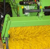Brush for cleaning the street. Yellow brush in a green metal frame attached to a tractor for cleaning the street royalty free stock images