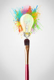 Brush close-up with colored paint splashes and lightbulb. Paintbrush close-up with colored paint splashes and lightbulb concept Stock Photo