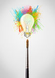 Brush close-up with colored paint splashes and lightbulb. Paintbrush close-up with colored paint splashes and lightbulb concept Stock Images