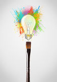 Brush close-up with colored paint splashes and lightbulb. Paintbrush close-up with colored paint splashes and lightbulb concept Royalty Free Stock Photo