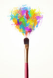 Brush close-up with colored paint splashes Stock Photography